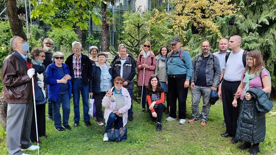 Egy csoportkép, melyen félkörívben látható 18 fő. Közülük ketten térdelnek. Háttérben szép zöld környezet.