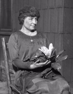 Helen Keller ül, kezében egy magnólia virággal